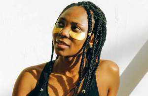 black woman with braids smiling with eye patches and black tank top