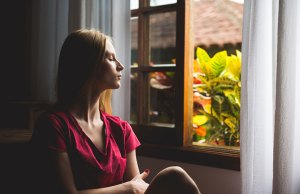 woman looking out of window at plants