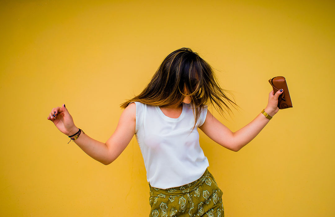 woman dancing in front of yellow wall