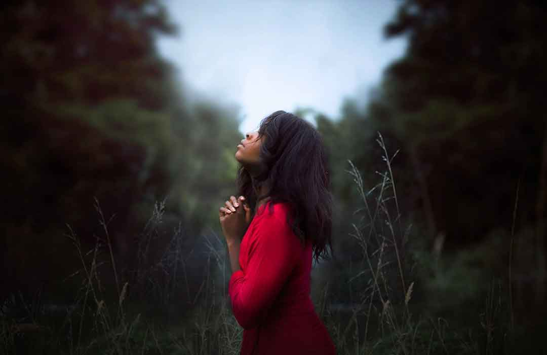 black woman in red dress looking up at blue sky in green brush