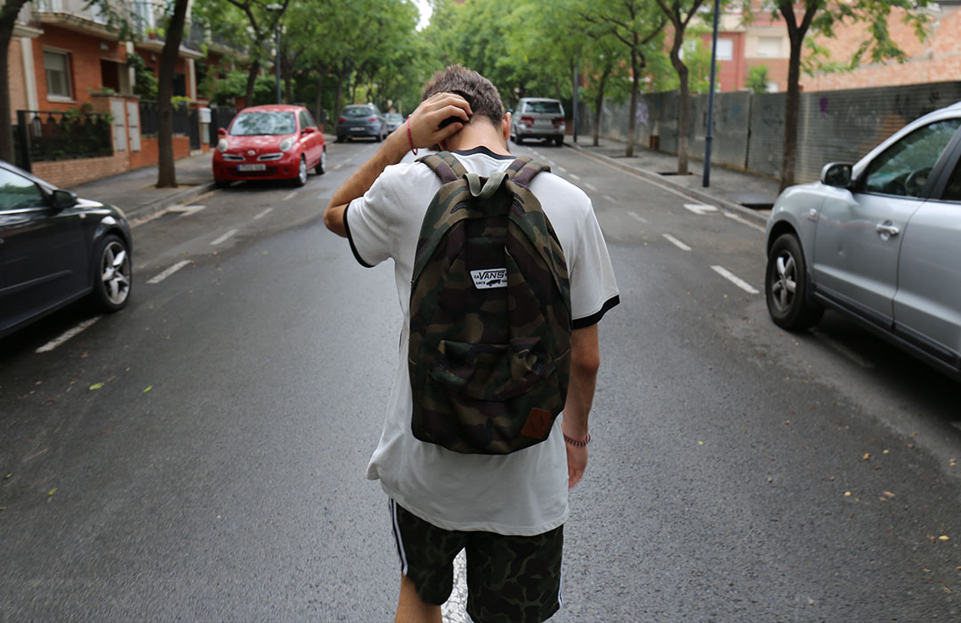 teen with backpack walking down street