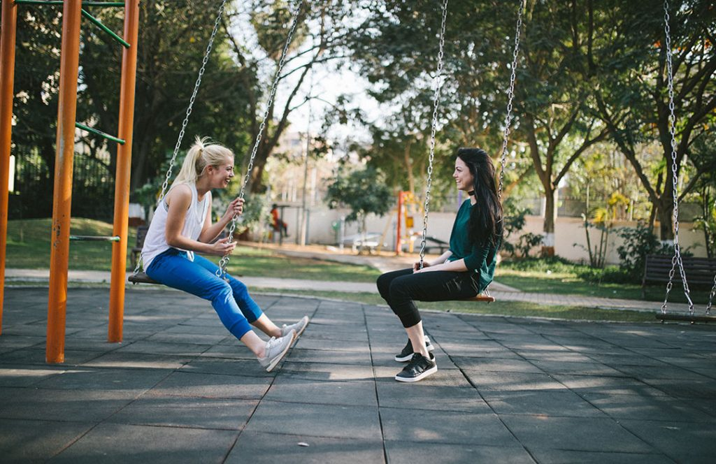 two woman on swings talking
