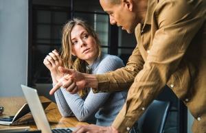 Man and woman talking at a computer