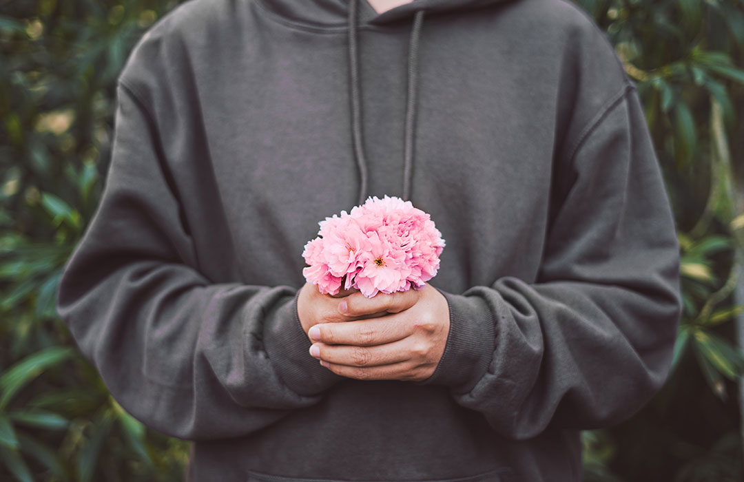man in grey sweatshirt holding pink flower