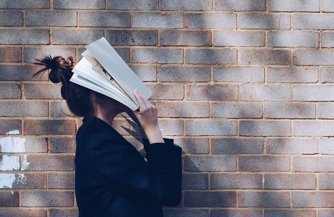 woman holding book against head on brick wall