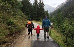 family walking on road in woods