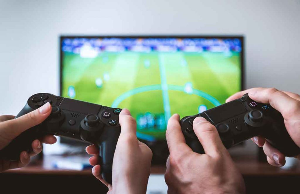 two gaming controllers in front of tv