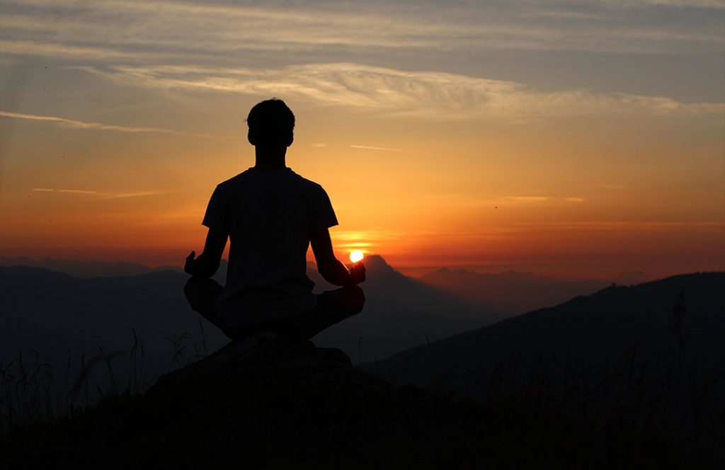 man meditating in front of an orange sunset