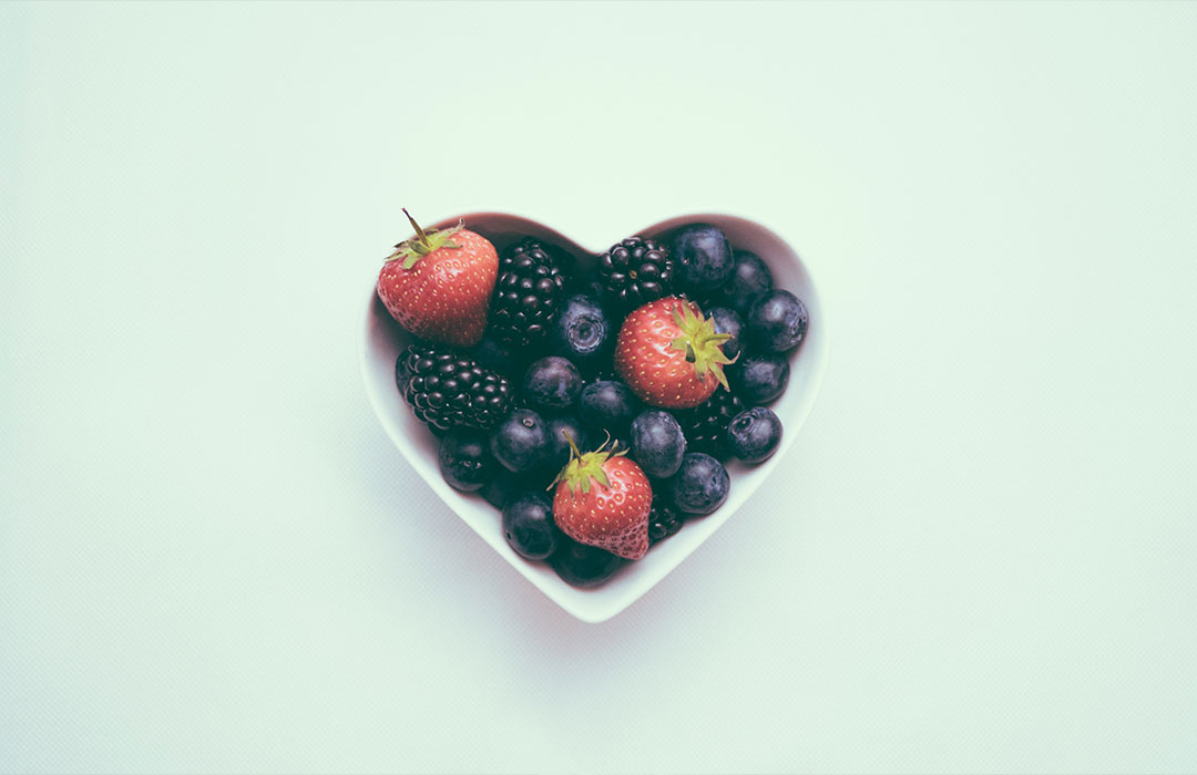 blueberries, blackberries and strawberries in heart shaped bowl