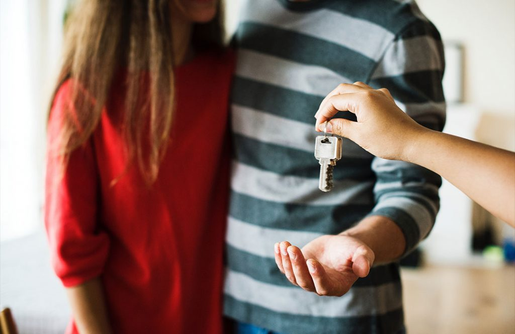 women in red shirt and man in blue stripe shirt handed house key
