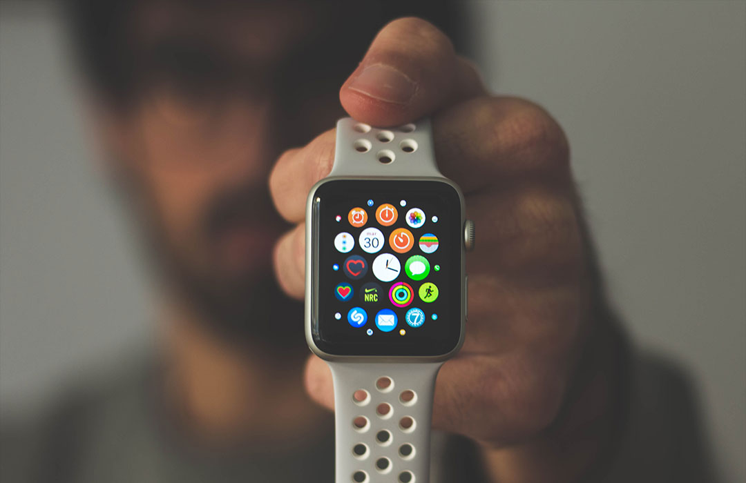 blurry man holding apple watch with holey band