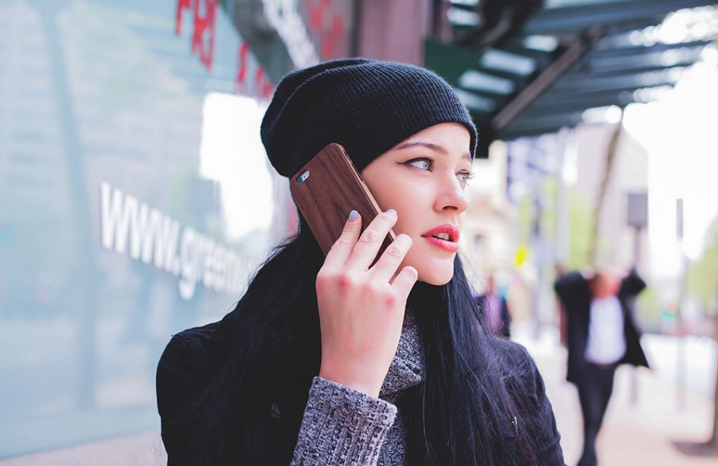 women in black hat with smart phone
