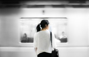 woman in white shirt standing in front of subway