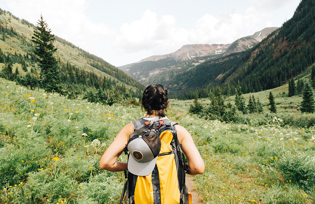 woman with yellow backpack on green mountains