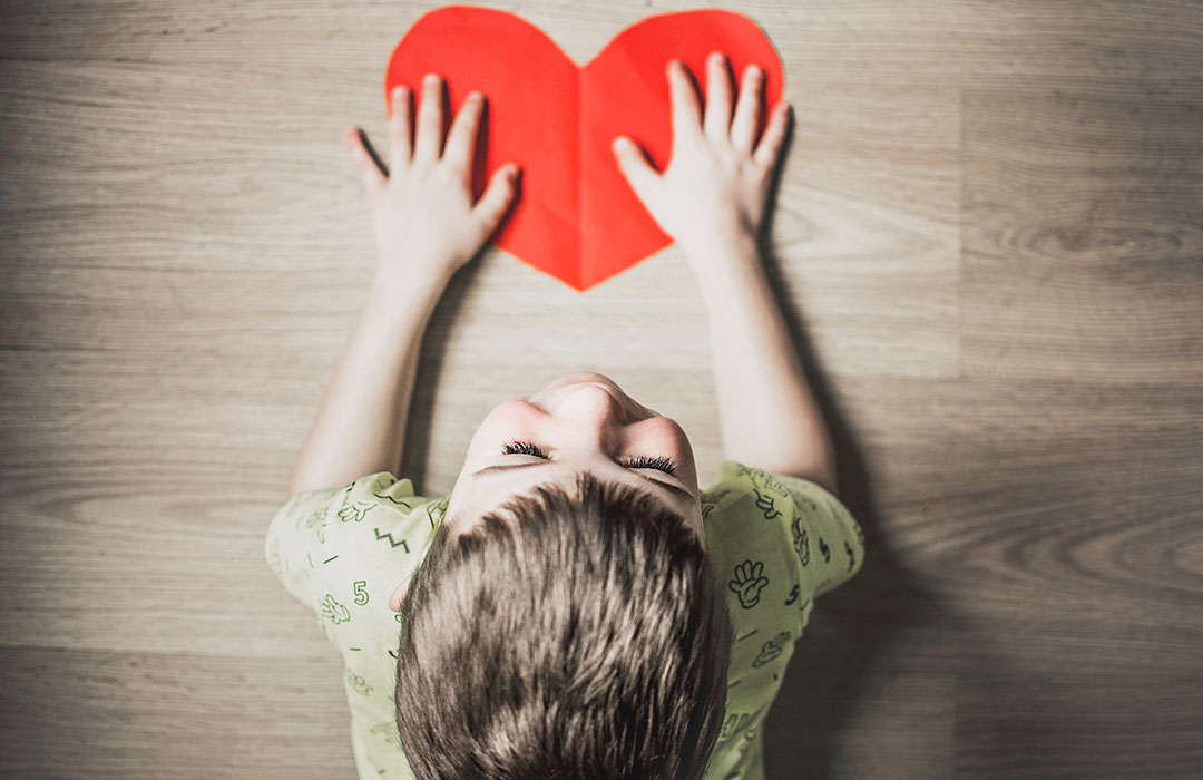 boy wearing green shirt with red paper heart