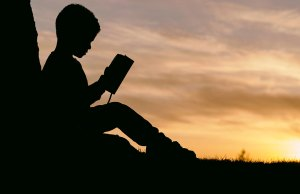 silhouette of child reading by sunset