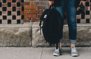 person in jeans standing with black backpack