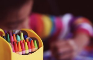 box of crayons and child drawing