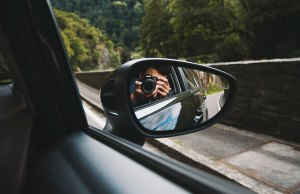 man taking picture in side view mirror