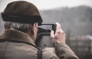 older man taking picture on cell phone