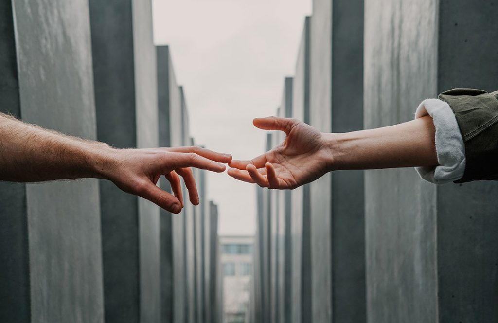 two hands touching in front of concrete structure