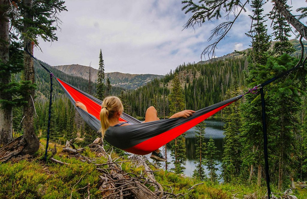 woman in red hammock in mountains