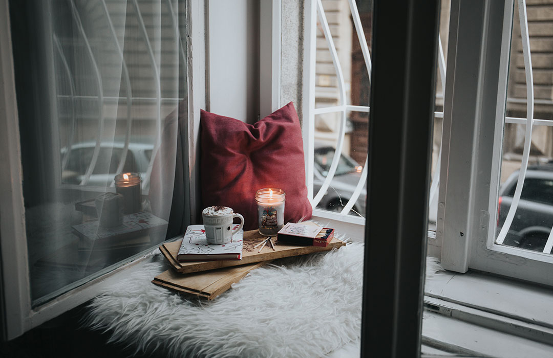 red pillow with books and candle
