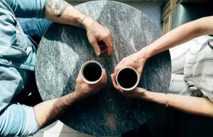 two people holding coffee on a grey table
