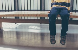 child in striped sweater sitting on bench