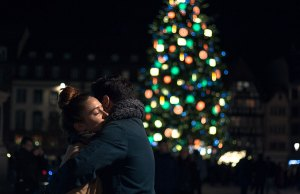 couple hugging by lit christmas tree
