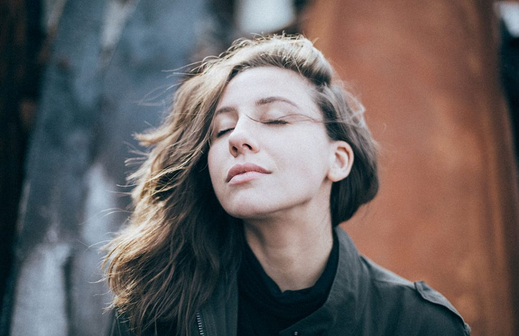 woman in black shirt closing eyes