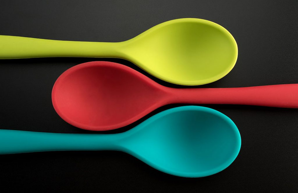 green, red and teal spoon on black background