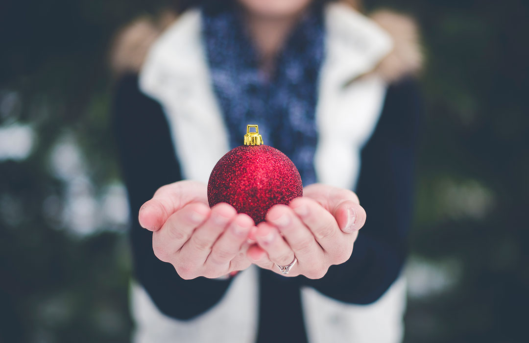 person in white vest holding red christmas ornament