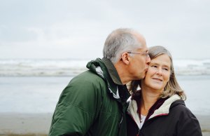 older couple kissing at beach