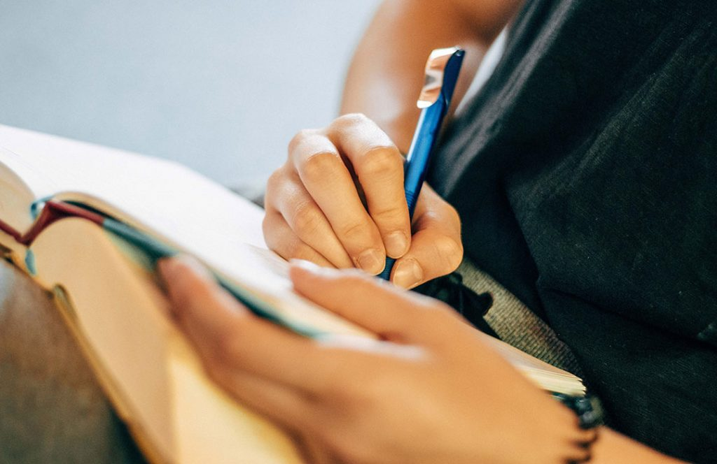 writing in a book with a blue pen
