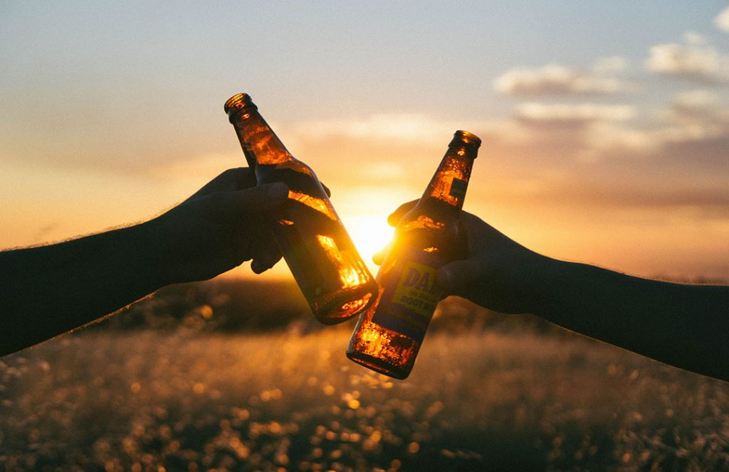 two beer bottles by sunset