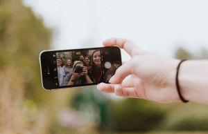 teenagers taking selfie in iphone screen