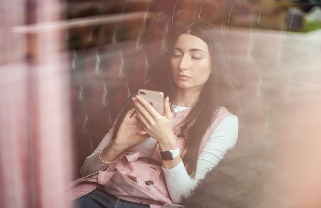 woman sitting down using an iphone