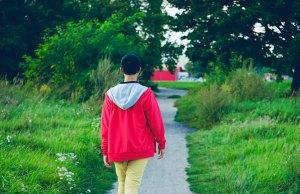 man in red jacket walking in grass