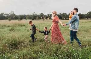 family walking through grass field