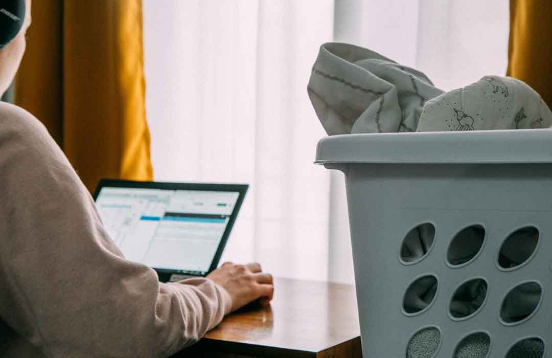 woman on laptop next to laundry basket