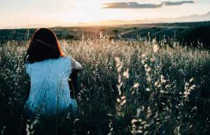 woman sitting in field looking at sunset