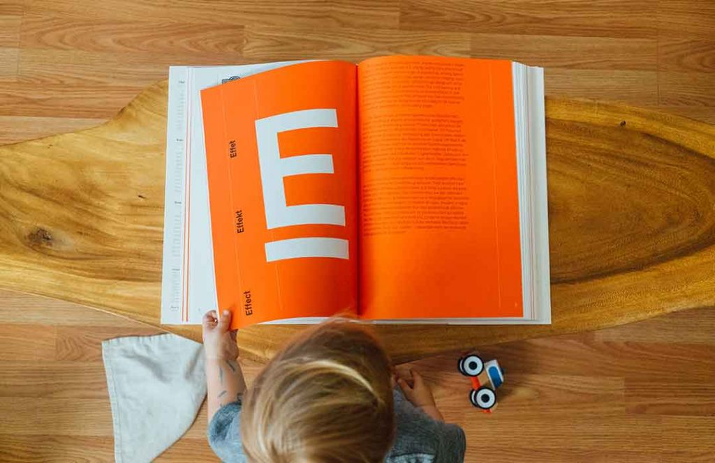 child reading orange book with letter e