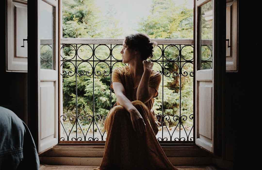 woman sitting in front of balcony with greenery
