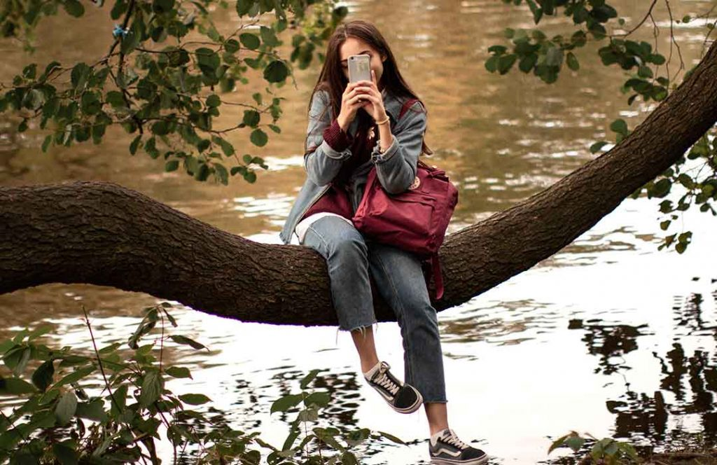 woman on phone sitting on tree branch