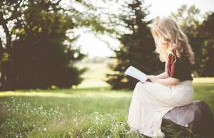 woman in white skirt reading book in grass