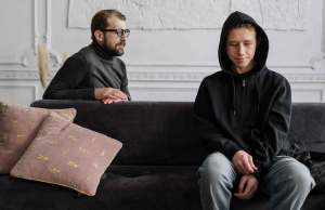 man and teenager in dark clothes on couch