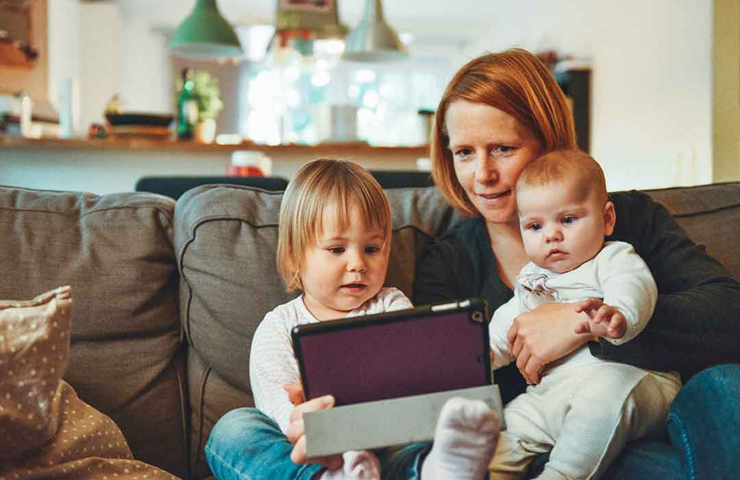woman with red hair with two babies in white holding ipad on brown couch