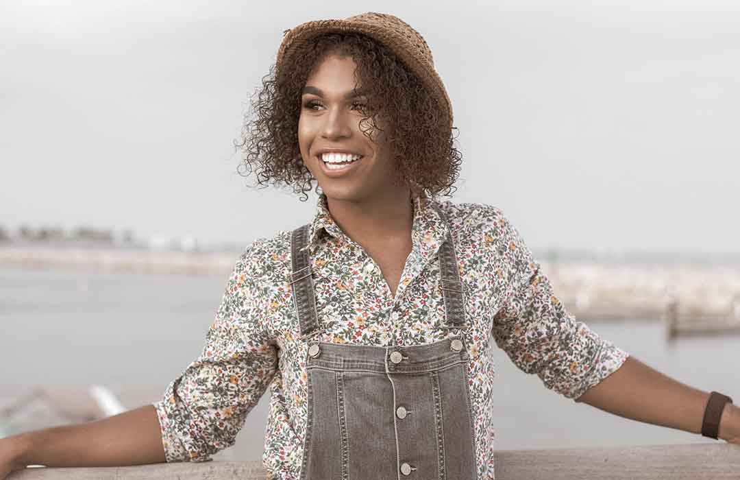 black woman with straw hat in white floral shirt under denim overalls outside of water
