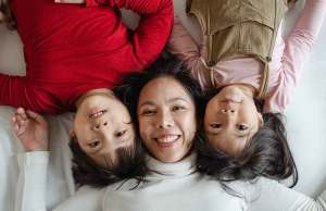 asian woman in white sweater laying with two asian children in red sweater and pink shirt